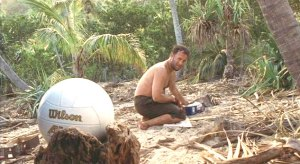 "Tom Hanks as Chuck Noland in the film ""Cast Away"" along with his inanimate volleyball friend Wilson."